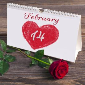 Saint Valentine calendar on rustic wooden table and red rose.  Font used is approved for commercial use.